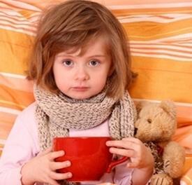 болеющая ангиной девочка держит в руках чашку