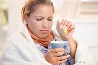 Простуженная женщина выжимает в чашку сок лимона
