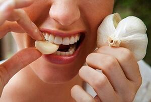 Женщина кусает зубчик чеснока