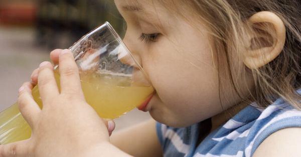Маленькая девочка пьет сок из стакана