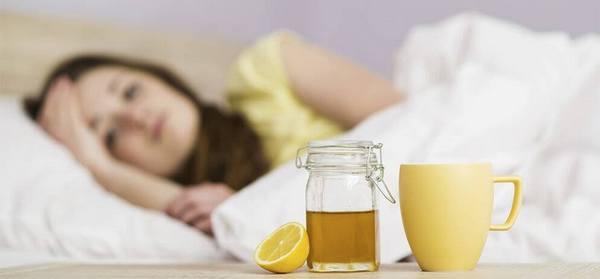 Чашка с напитком стоит рядом с простуженной девушкой
