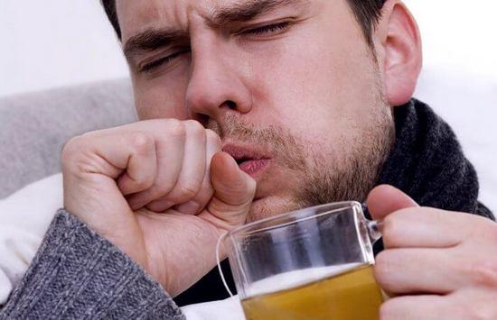 Кашляющий мужчина пьет лечебный напиток