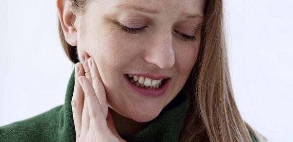 Женщина держится за зубы