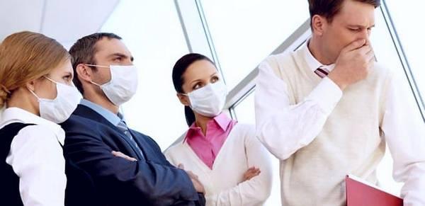 Люди в гигиенических масках смотрят на чихающего коллегу