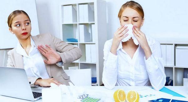 В офисе женщина отстраняется от сморкающейся коллеги