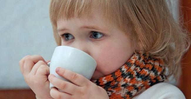 Девочка с больным горлом пьет из чашки