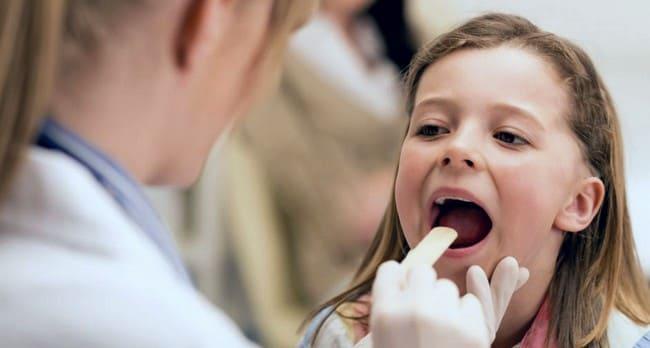 Женщина-врач осматривает горло девочки