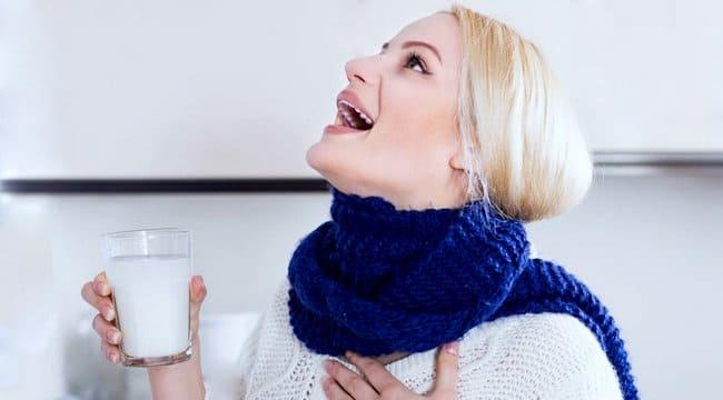 Женщина полощет горло содовым раствором