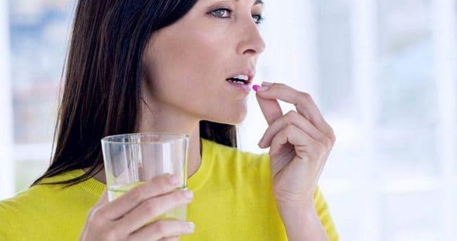 Молодая женщина пьет таблетку