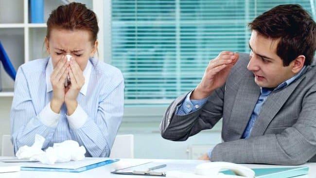 В офисе мужчина опасается заразиться от сморкающейся женщины