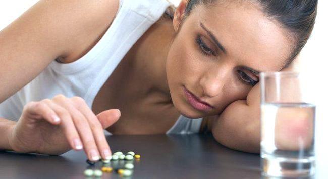 Женщина перебирает рассыпанные перед ней на столе таблетки