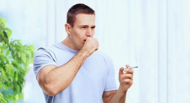 Молодой человек с сигаретой кашляет в кулак