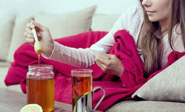 Девушка на диване хочет добавить мёд в чай