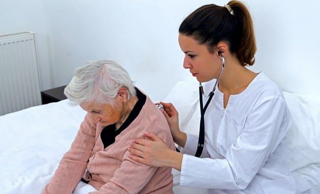 Медсестра слушает дыхание пожилой женщины фонендоскопом