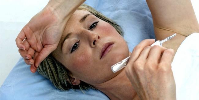 Женщина болезненного вида смотрит на градусник