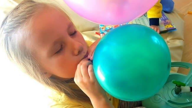 Девочка надувает воздушный шарик