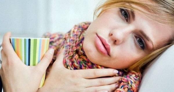 Женщина с намотанным на горло шарфом лежит в постели